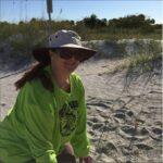 Sea Turtle Trackers Volunteer on the beach near some sea oats.